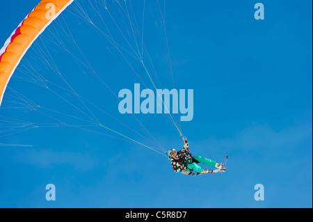Una femmina di parapendio in un alto powered girare sorrisi. Immagini Stock