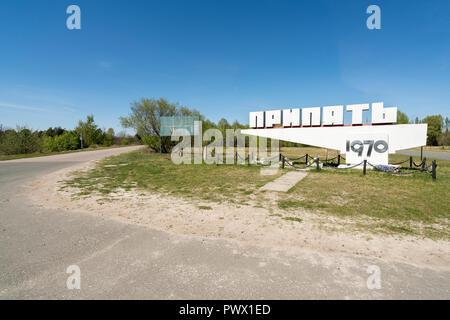 Il segno della città di pripjat con la strada che conduce verso di esso di Chernobyl, in Ucraina. Immagini Stock