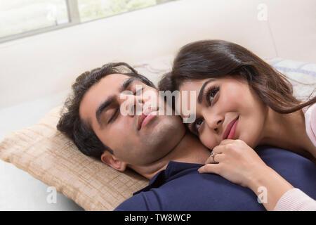 Coppia giovane sdraiato sul letto Immagini Stock