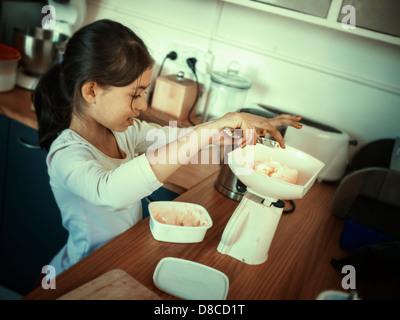 Home cottura, ragazza pesa la margarina con bilancia da cucina. Immagini Stock