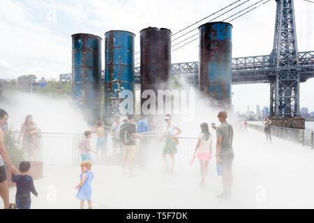 Visitatori sul ponte di nebbia la funzione con il Williamsburg Bridge in background. Domino Park, Brooklyn, Stati Uniti. Architetto: James Corner Field ope Immagini Stock