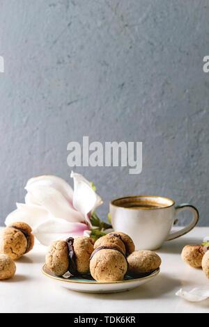 Baci di dama casalingo italiano biscotti di nocciole biscotti con crema di cioccolato servita nella piastra in ceramica con tazza di caffè espresso e di fiori di magnolia Immagini Stock