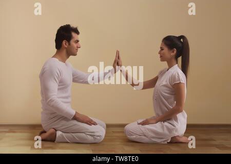 Coppia giovane di eseguire lo yoga faccia a faccia a contatto con le mani Immagini Stock