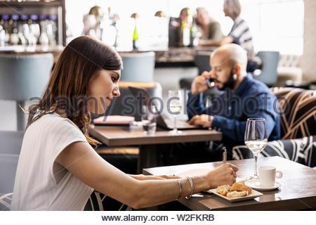 Imprenditrice lavorando in bar Immagini Stock