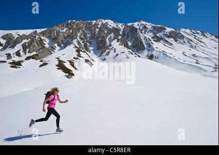 Un pareggiatore di corsa attraverso una montagna innevata gamma. Immagini Stock
