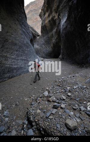 Escursionista esplorare formazioni rocciose, Marble Canyon, il Parco Nazionale della Valle della Morte, California Immagini Stock