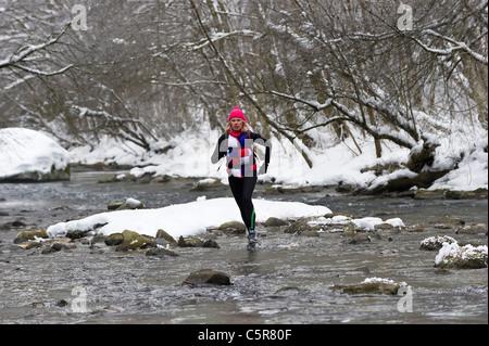 Un pareggiatore che attraversa un fiume nevoso. Immagini Stock