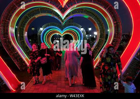 Donne locali a piedi di notte attraverso una illuminata a forma di cuore in tunnel Tsvetochny o fiore parco nel centro di Grozny capitale della Cecenia ufficialmente la Repubblica cecena nel Nord Caucaso Distretto federale della Russia. Immagini Stock