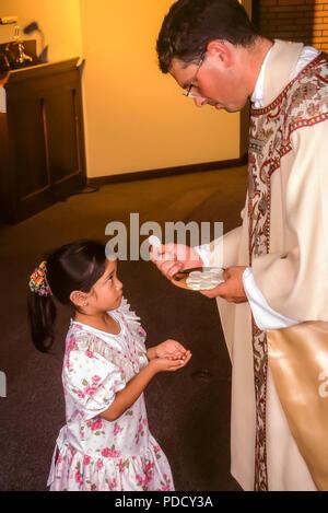 Piccola ragazza riceve la Comunione wafer dal sacerdote. Il sig. © Myrleen Pearson .........Ferguson Cate Immagini Stock