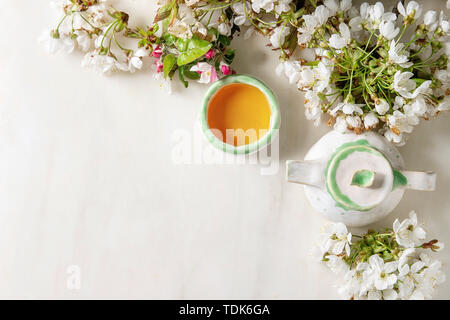 Artigianato Ceramiche Artigianali teiera e tazza di tè caldo decorato da primavera sbocciano i fiori ciliegio rami su marmo bianco dello sfondo. Laici piana, spazio Immagini Stock
