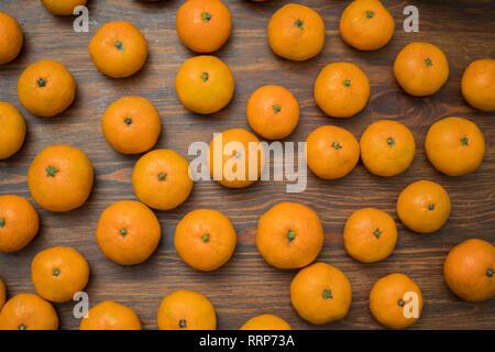 Succosa arancio brillante tangerini su uno sfondo di legno. Set di frutta. Sfondo Immagini Stock