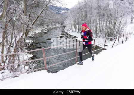 Una donna jogging su un ponte al di sopra di un inverno nevoso sul fiume. Immagini Stock