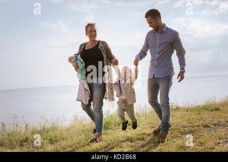 I genitori con figli (0-1 mesi 18-23 mesi) passeggiate in mare Immagini Stock