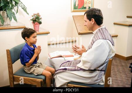 Ragazzo con il sacerdote nella riconciliazione il sig. © Myrleen Pearson ....Ferguson Cate Immagini Stock