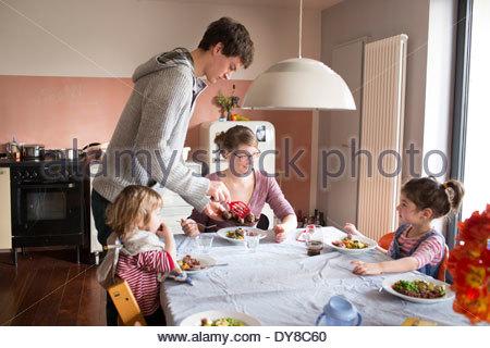 I giovani genitori a mangiare il pranzo con i loro figli Immagini Stock