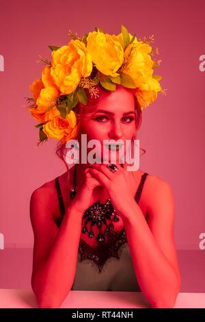 Moda ritratto di una bellissima ragazza con una ghirlanda di fiori e brillante trucco. Filtro colore Immagini Stock