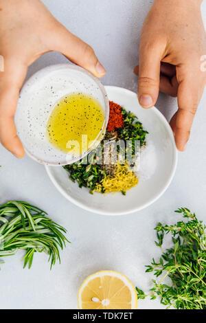 Donna versando olio d'oliva in bacchette di Pollo Marinato Ingredienti Immagini Stock