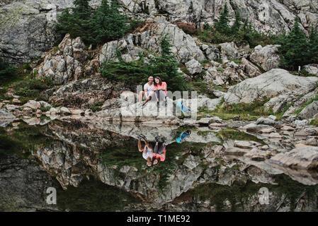 Ritratto giovane escursionismo, appoggiata al lago roccioso, cane montagna, BC, Canada Immagini Stock