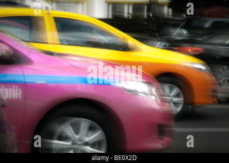 Thailandia, Bangkok, hot pink taxi in movimento sfocate di arancio e giallo taxi al di là Immagini Stock