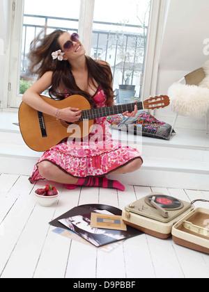 Bruna giovane donna a suonare la chitarra a casa Immagini Stock