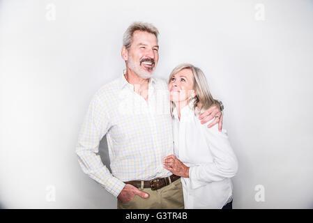 Una coppia matura in posa di un studio cercando felice. Immagini Stock
