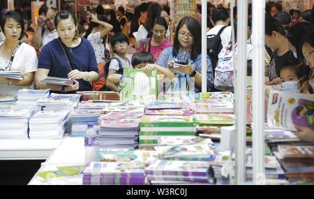 (190717) -- HONG KONG, luglio 17, 2019 (Xinhua) -- i genitori e i bambini selezionare libri durante il trentesimo Hong Kong Fiera del Libro di Hong Kong, Cina del Sud, 17 luglio 2019. Il trentesimo Hong Kong Book Fair aperto mercoledì presso il Centro Convegni ed Esposizioni di Hong Kong. Quest'anno la fiera del libro attira 686 espositori provenienti da 39 paesi e regioni. (Xinhua/Wang Shen) Immagini Stock