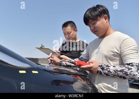 """(190717) -- TURPAN, luglio 17, 2019 (Xinhua) -- ricercatori testare un auto della pellicola di vernice al Xinjiang Turpan Ambiente Naturale Experimental Research Center di Turpan, a nord-ovest della Cina di Xinjiang Uygur Regione autonoma, 17 luglio 2019. Conosciuta come """"la terra di fuoco"""" con la sua estremamente caldo e il clima è secco, Turpan nel nord ovest della Cina è diventata una delle scelte migliori per il mondo società automobilistica, materiale i fabbricanti e gli istituti di ricerca che cercano un esperimento terreno per condurre prove ad alta temperatura sui veicoli. Attualmente, oltre 30.000 articoli sono sotto la luce diretta del sole prove di esposizione whil Immagini Stock"""