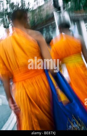Thailandia, Bangkok, Wat Suthat tempio, due arancio-derubato, giovane debuttante monaci a piedi attraverso il tempio Immagini Stock