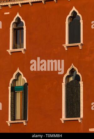 Venetian Windows su un rosso casa storica, della Regione del Veneto, Venezia, Italia Immagini Stock