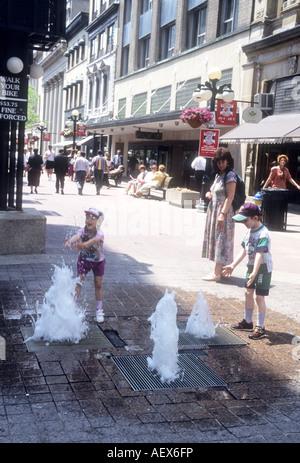 I bambini godono di una divertente funzione di acqua in un pedone,Centro commerciale a Ottawa, Ontario, Canada Immagini Stock