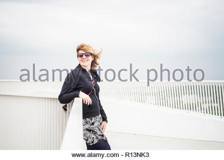 Una giovane donna che indossa gli occhiali da sole in piedi da una ringhiera Immagini Stock