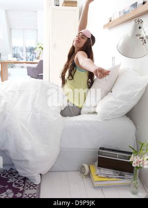 Giovane donna nel letto risveglio Immagini Stock