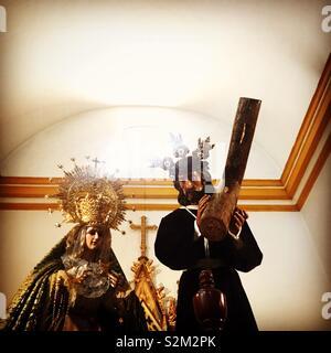 Le immagini della Vergine Maria e Gesù Cristo che porta la croce sono visualizzati in una chiesa in Prado del Rey, Sierra de Cadice, Andalusia, Spagna Immagini Stock