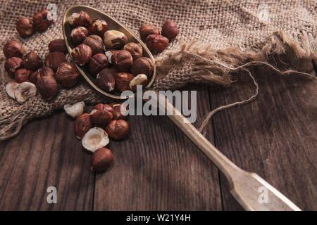 Le nocciole su un vecchio cucchiaio e composizione dal vecchio legno e materiali Immagini Stock