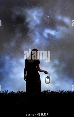 Una donna nel buio con una lanterna Immagini Stock