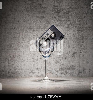 Mix di musica per una festa. Mixed Tape in un bicchiere da cocktail. Ancora vita con il simbolo degli anni ottanta Immagini Stock