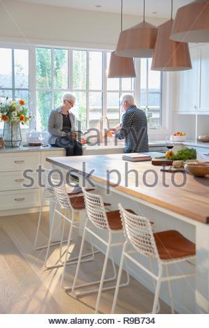 Coppia senior per la cottura, la lettura di un libro di cucina in cucina Immagini Stock