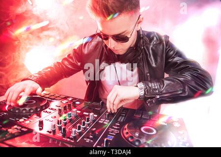 Il mixaggio DJ al party festival con la luce rossa e il fumo in background - Estate vista notturna della discoteca all'interno. Focus sulla faccia Immagini Stock