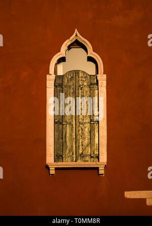 Finestra veneziana su un rosso casa storica, della Regione del Veneto, Venezia, Italia Immagini Stock