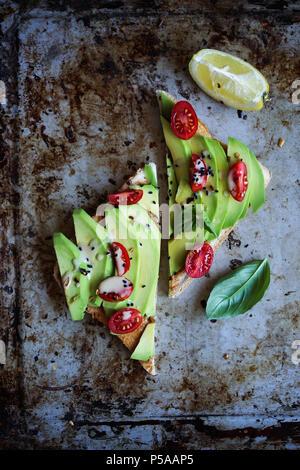 Un semplice e delizioso avotoast con pomodorini e salsa di tahina. Immagini Stock