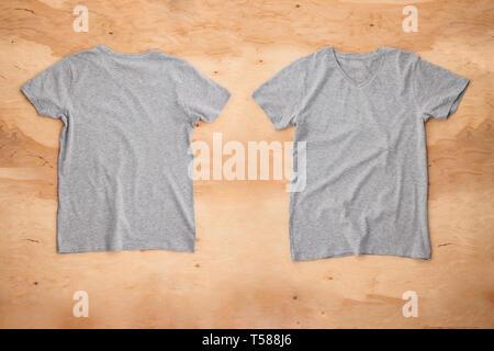 Parte anteriore e posteriore del grigio melange svuotare T-shirt su sfondo di legno. Vista orizzontale. Immagini Stock
