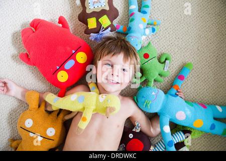 Ragazzo giovane coperto in giocattoli imbottiti Immagini Stock
