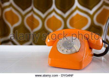 Vecchio telefono arancione con manopola Immagini Stock