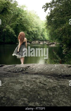 La donna nel lungo abito di sun al lago Immagini Stock