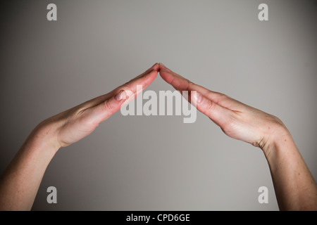 Due mani formando un ponte o del tetto Immagini Stock