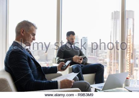 Gli operatori, con tavoletta digitale e smart phone in ufficio urbano lounge Immagini Stock