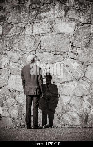 Il vecchio uomo in piedi di fronte a muro di pietra. Sole e ombra pesante. Edificio esterno con spazio copia. Immagini Stock
