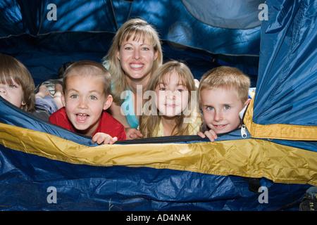 Una donna e un gruppo di bambini sdraiati in una tenda Immagini Stock