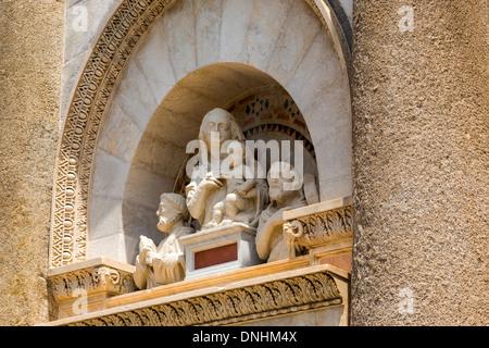 Statua scolpita in corrispondenza di una torre, la Torre Pendente di Pisa e Piazza dei Miracoli a Pisa, Toscana, Italia Immagini Stock