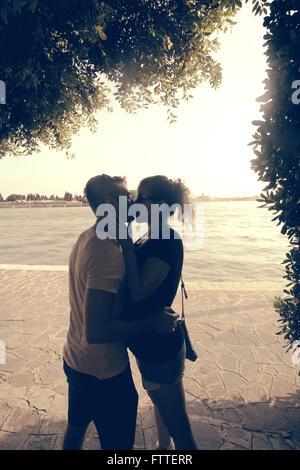 Coppia giovane kissing in ombra Immagini Stock